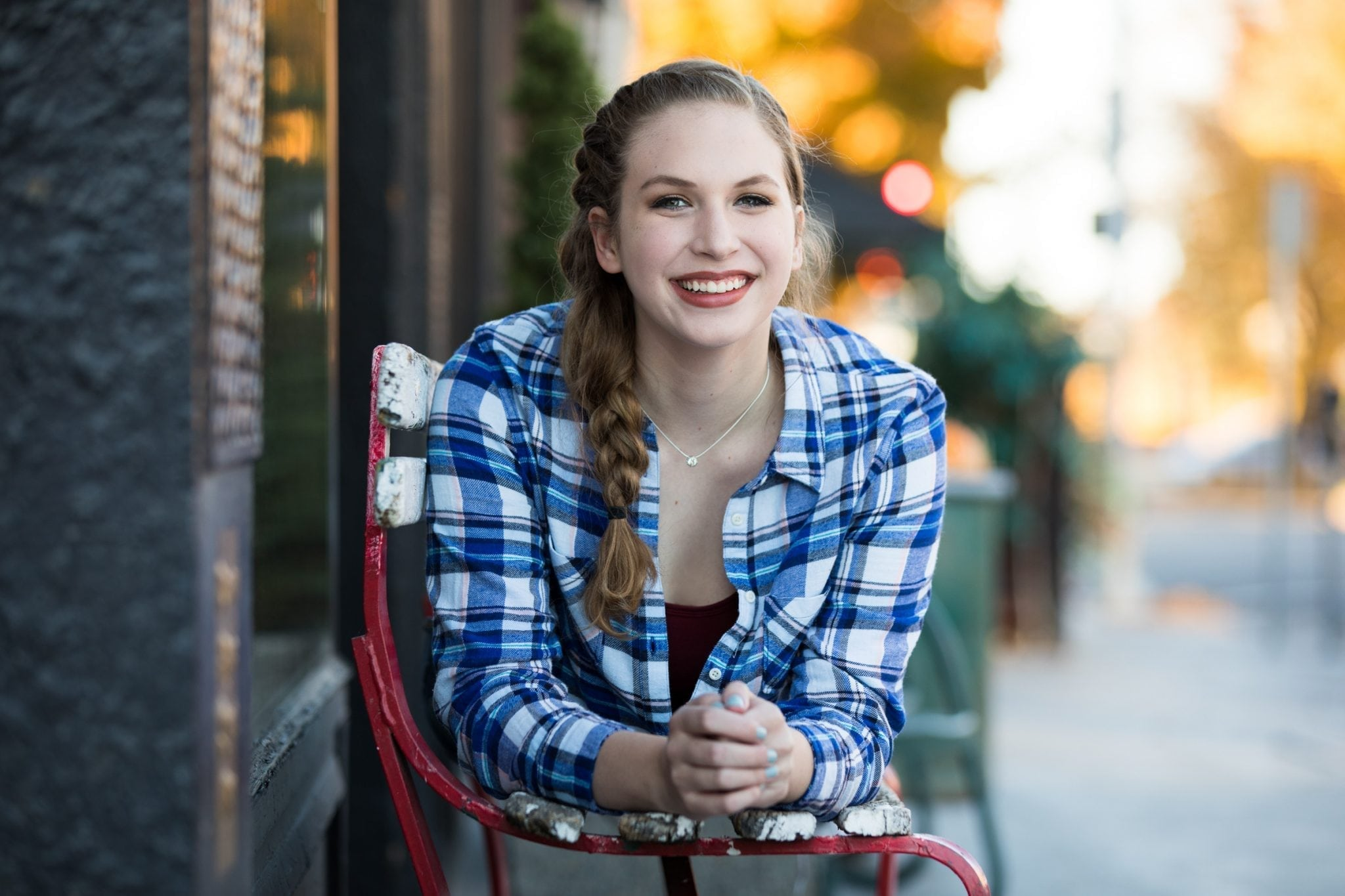 Cute senior photo of a girl laying on a bench in downtown Spokane.