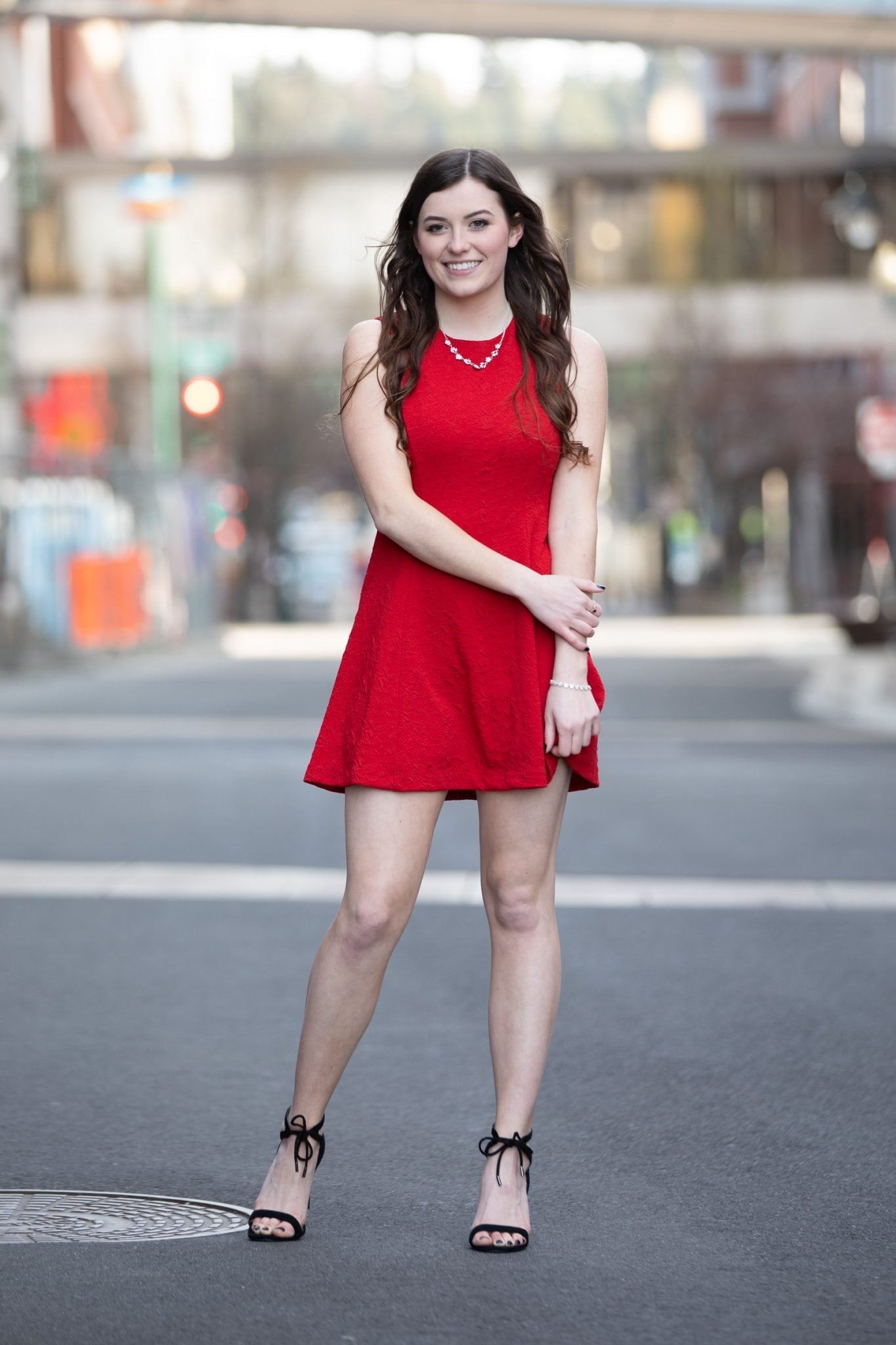 senior photo of girl in red dress in street during photo shoot